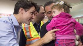 """Handsome Canadian Prime Minister greets adorable Syrian refugees."""